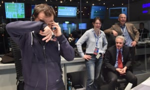 Rosetta's flight director, Andrea Accomazzo,, left,  takes a call after receiving confirmation that the Philae lander had successfully touched down.