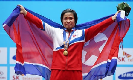 Gold medalist Kim Un-ju lifts the North Korean flag following the women's 75kg weightlifting final.
