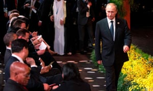 Vladimir Putin arrives at the Welcome to Country ceremony at the G20 summit as other world leaders sit.