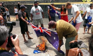 Indigenous rights protesters burn Australian national flags during a rally on the sidelines of the G20 summit in Brisbane, Australia 16 November 2014.