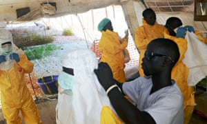 MSF doctors put on protective gear at an Ebola isolation ward in Guinea. Photograph: Cellou Binani/A