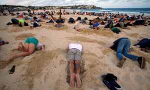 About 400 people bury their heads in the sand at Sydney's Bondi Beach ahead of the G20 summit in Brisbane. The group were protesting Australia's reluctance to place climate change firmly on the meeting's agenda.