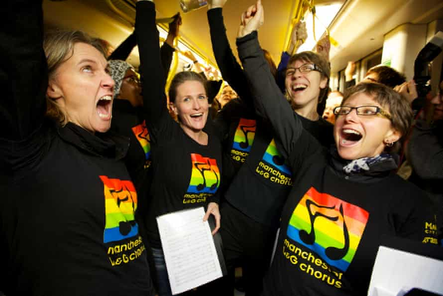 Members of the Manchester Lesbian and Gay Chorus singing on Metrolink trams in Manchester city centre