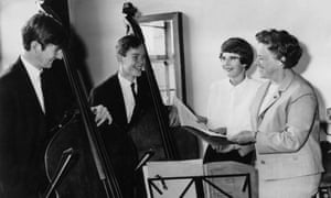 Ivey Dickson, smiling, with double bass players, National Youth Orchestra of Great Britain