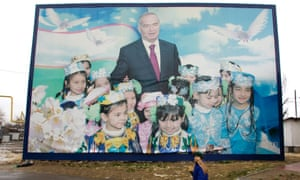 A boy walks past a poster of Uzbekistan's President Islam Karimov in Tashkent December 23, 2007.