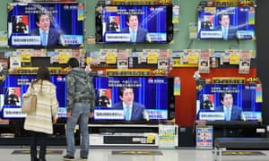 A couple watch television news  broadcasting Japanese Prime Minister Shinzo Abe holds a press conference to announce that he is delaying a tax hike and dissolving the lower house of parliament