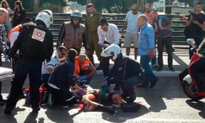 Israeli medics treat a wounded soldier at the scene of a stabbing attack in Tel Aviv.