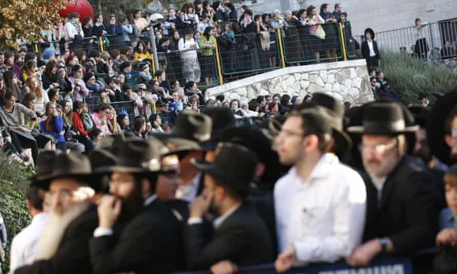 Ultra-orthodox Jews watch emergency personnel clean up and secure the area of the attack.