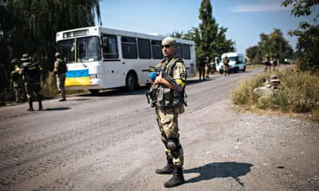 A Ukrainian soldier stands guard in Maryinka, near Donetsk, Ukraine
