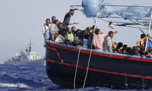 Migrants are taken to the mainland after being rescued by an Italian navy boat.