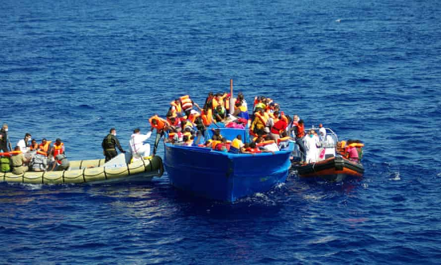 Rescuers from the Italian navy help migrants climb on their boat in the Mediterranean.