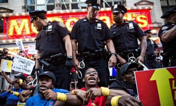 Fast-food workers demanding higher wages and unionisation block traffic near Times Square, NYC