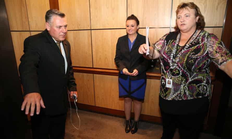 Staff shield Jacqui Lambie from reporters as she leaves a press conference in parliament on Wednesday.