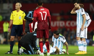 Angel Di Maria sits on the Old Trafford turf with a grimace after injuring his groin in Argentina's friendly with Portugal.