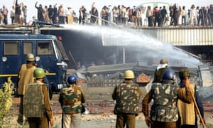Indian police use water cannon to scatter supporters of self-styled guru Sant Rampal during an attempt to storm his compound.