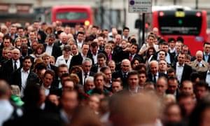 Commuters walk across London Bridge during morning rush hour