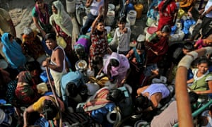 Residents of a slum in New Delhi crowd around a tanker delivering drinking water.
