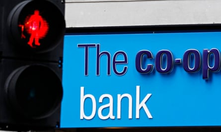A red crossing light is pictured next to a branch of the Co-operative Bank in London