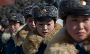 Female North Korean traffic police officers gather in front of bronze statues of the late leaders Kim Il Sung and Kim Jong Il to pay their respects in Pyongyang, North Korea on Saturday, Feb. 16, 2013.