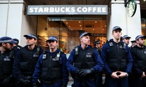 Police officers guard a Starbucks during a protest against fees.