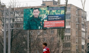 A man walks past a hoarding in Donetsk, Ukraine, with a portrait of Alexander Zakharchenko