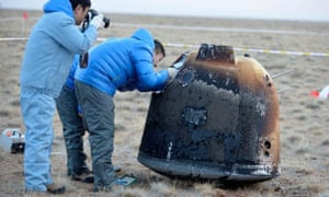 Chinese researchers examine the scorched Chang'e 5-T1 return capsule after it landed successfully in Inner Mongolia having travelled around the moon and back.