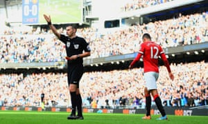 Chris Smalling walks away having been sent off by referee Michael Oliver.