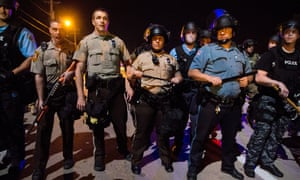 Police officers in riot gear patrol demonstrators in Ferguson, Missouri, during the civil unrest in August.