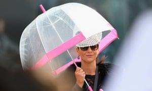 A spectator shields herself under an umbrella.