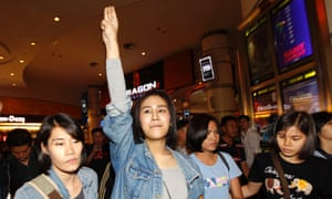 Pro-democracy activist Nacha Kong-udom is detained by female plain clothed police officers at a cinema in Bangkok on 20 November.