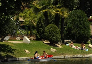 People sunbath at the lake of the Casa de Campo park on a hot spring day in Madrid on June 13, 2009. Temperatures reached 36C in the Spanish capital.