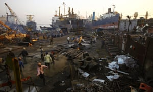 Workers break huge ships down for scrap in the Mumbai dockland area.