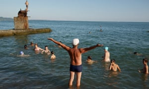 Swimming instructor Victor Zadarozhny demonstrates backstroke to his young students on the beach at Sukhumi. In Soviet days he taught in a nearby swimming pool but the war and subsequent economic collapse ruined the facility