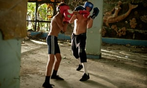 Boxing trainer Lizbar Jalogua spars with a young student in a ruined Soviet Resort in Gagra