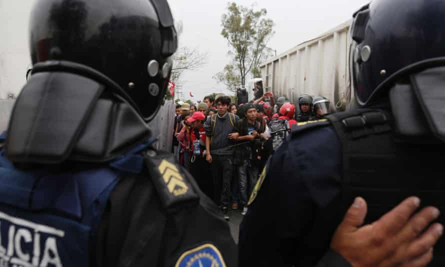 Riot police escort demonstrators during a protest over the 43 missing students in Mexico City .