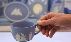 A woman holds a Wedgwood teacup featuring the white and blue ceramic synonymous with the brand.