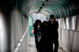 Iranians cover their noses and mouths to protect themselves from pollution as they walk across a pedestrian bridge in a northern district of Tehran on December 5, 2012.