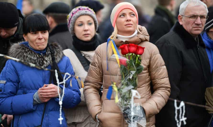 Ukrainian anti-government demonstrators pay their respects at a memorial for protesters killed in clashes with police in Independence Square.