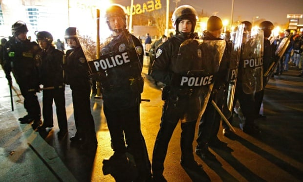 Police rush in to break up protesters outside the Ferguson police station in Ferguson, Missouri, 20 November 2014.