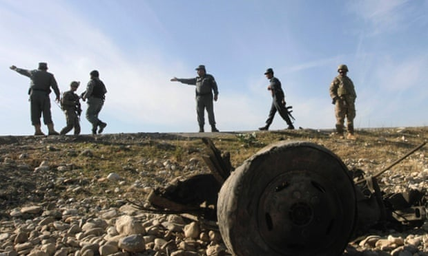 US troops and Afghan police officers at the site of a suicide attack on the outskirts of Jalalabad on 13 November 2014.