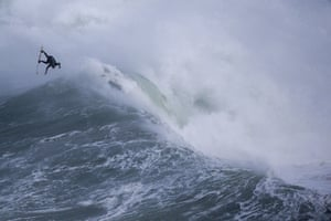 A surfer rides a wave at Praia do Norte in Nazare.