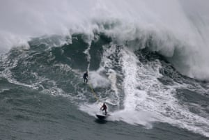 An unidentified surfer is towed in to a huge wave.