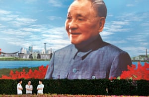 Tourists stand in front of a painting of the late leader of the Communist Party.