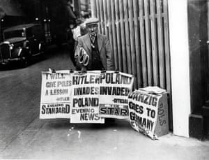 A newspaper vendor displays posters of the headlines announcing Adolf Hitler's invasion of Poland