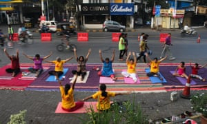 People perform yoga on the usually chaotic and congested Linking Road.
