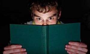 A man reading a book at night