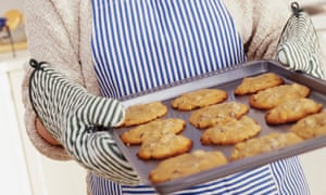 Oven gloves holding a tray of biscuits