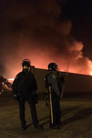 Troopers guarding the burning remains of beauty store and Metro PCS on W Florissant