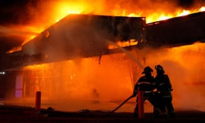 Firefighters work to extinguish a blaze, set by protester, at a Little Caesar's restaurant in Ferguson, Missouri.