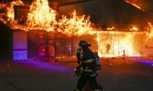 A firefighter arrives to inspect a pizza business set ablaze in Ferguson, Missouri.